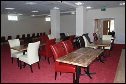 Photograph of the social club interior looking toward the soft seating area and big screen TV